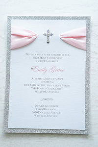 "alt=""Elegant silver glitter First Communion invitation features a white pearlescent shimmer card stock on a silver glitter stock, a rich pink satin ribbon and an elegant cross and jewel detail"""