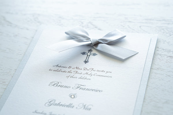 "alt=""Classic embellished First Communion invitation features a white pearlescent shimmer card stock on silver pearlescent shimmer card stock, an elegant cross and jewel detail finished with a rich silver satin ribbon bow"""