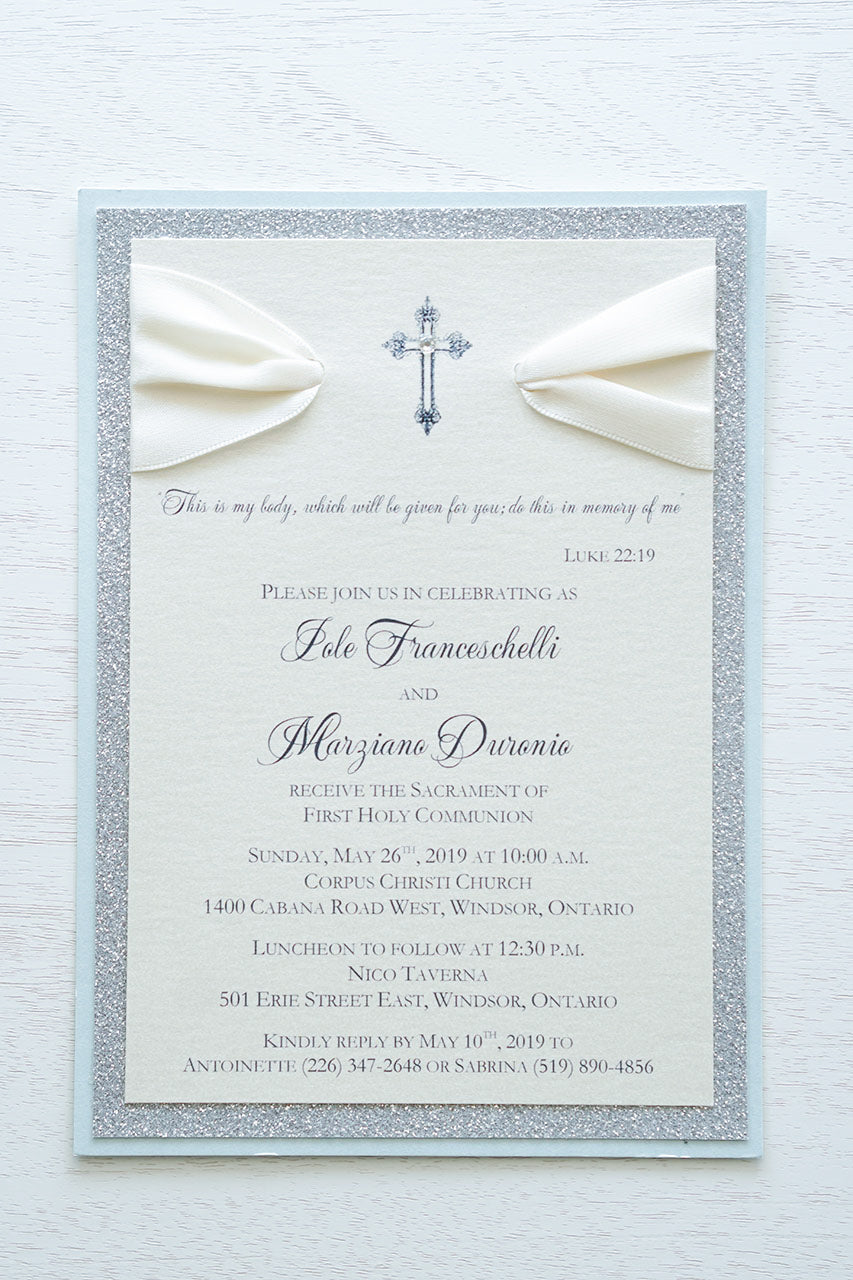 "alt=""Elegant glitter First Communion invitation features an ivory pearlescent shimmer card stock on blue pearlescent shimmer and silver glitter card stock, an elegant cross and jewel detail finished with a rich ivory satin ribbon"""