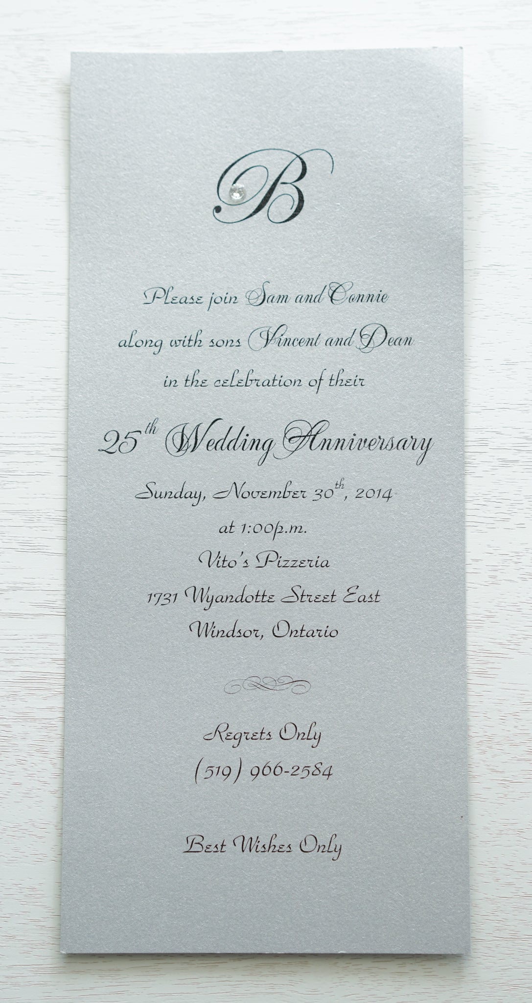 "alt=""Simplistic 25th Wedding Anniversary invitation features a silver pearlescent shimmer card stock and an elegant monogram and jewel detail"""