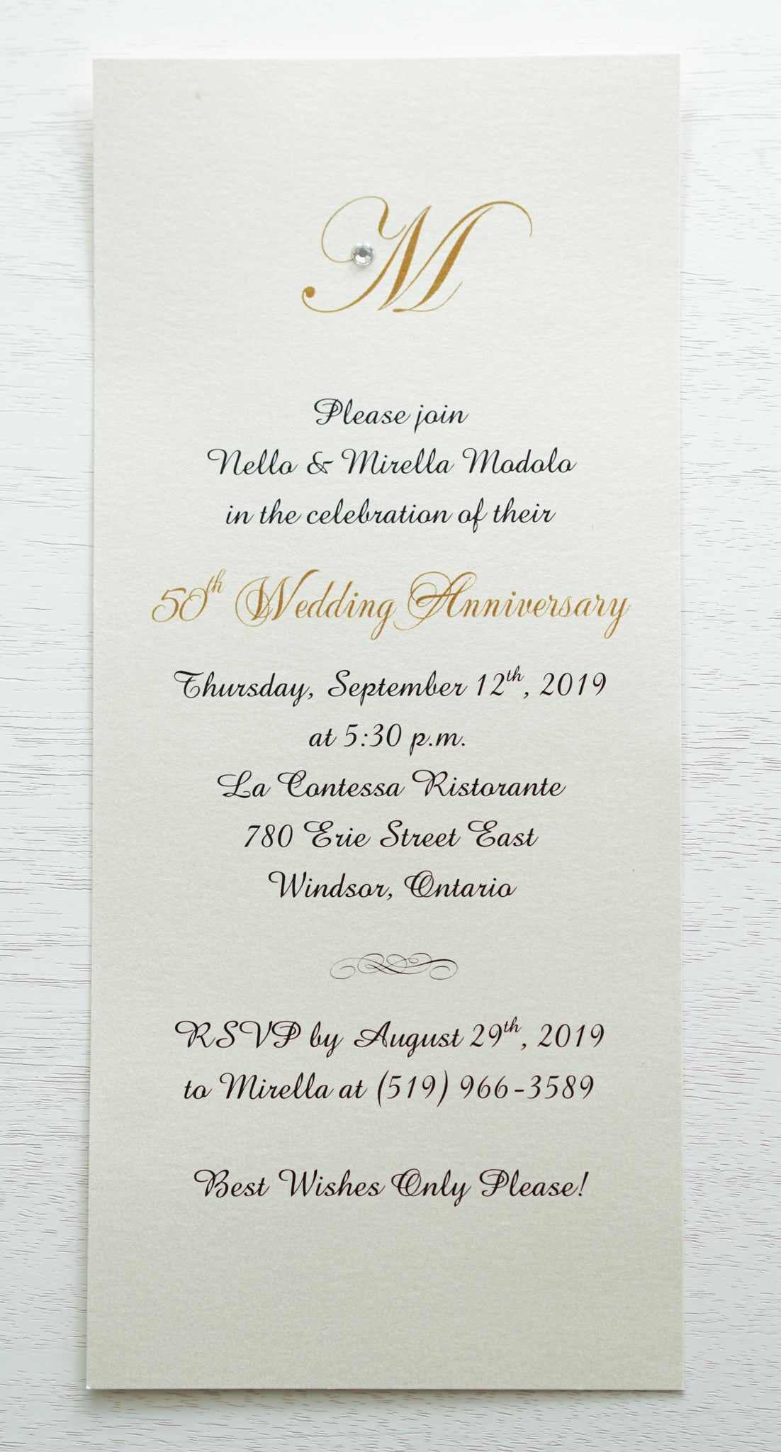 "alt=""Simplistic 50th Wedding Anniversary invitation features an ivory pearlescent shimmer card stock and an elegant gold monogram and jewel detail"""