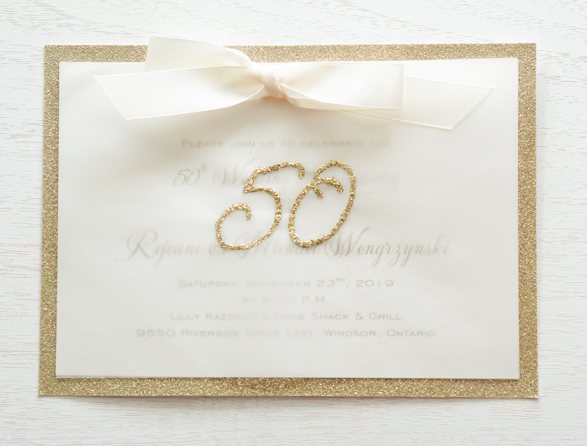 "alt=""Elegant 50th Wedding Anniversary invitation features a vellum layer on ivory pearlescent shimmer and gold glitter card stock, an elegant gold glitter 50th sparkle detail and is finished together with a rich ivory satin ribbon bow"""