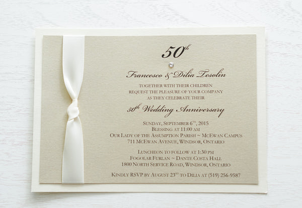 "alt=""Classy 50th Wedding Anniversary invitation features a champagne gold pearlescent shimmer card stock on an ivory pearlescent shimmer card stock, an elegant 50th and jewel detail and is finished with a rich ivory knotted ribbon"""