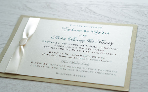 "alt=""Classic birthday invitation features an ivory pearlescent shimmer card stock on a champagne gold stock and a rich ivory satin knotted ribbon detail"""