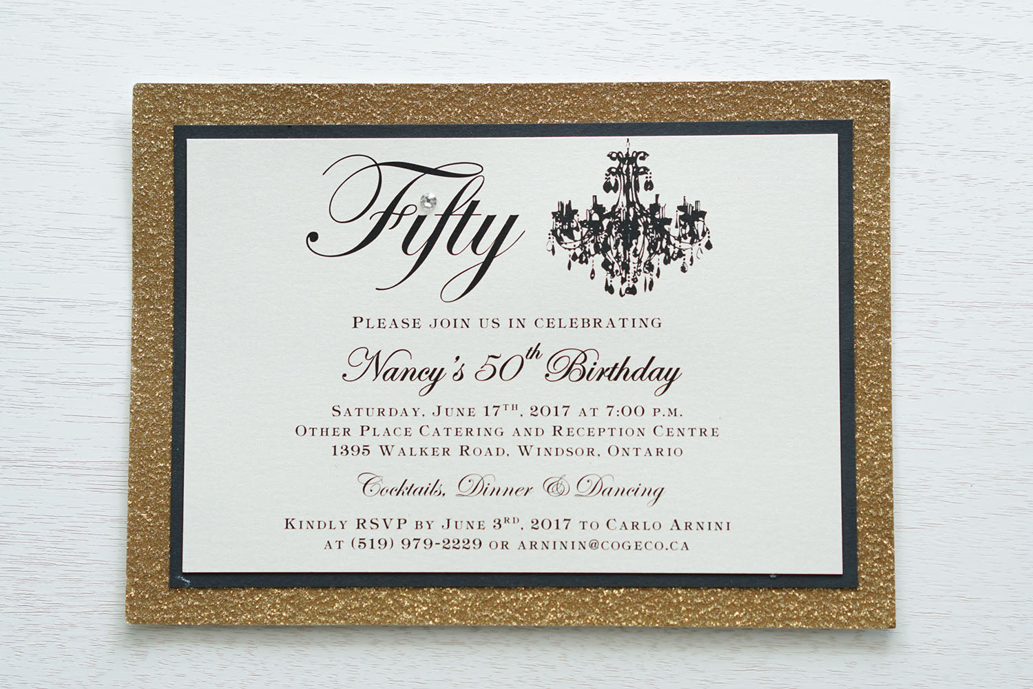 "alt=""Elegant birthday invitation features an ivory pearlescent shimmer card stock on matte black and gold glitter card stock, a beautiful chandelier image, fifty written in script and is finished with a jewel detail"""