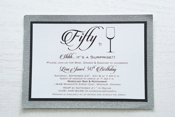 "alt=""Modern birthday invitation features a white pearlescent shimmer card stock on matte black and silver glitter card stock, a fun wine glass image, fifty written in script and is finished with a jewel detail"""