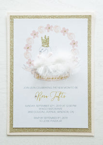 "alt=""Whimsical baby shower invitation features white pearlescent shimmer, gold glitter and soft pink card stock with a sweet swan and floral detail with a white feather, a rich pink satin ribbon and jewel accent and a gold glitter crown"""