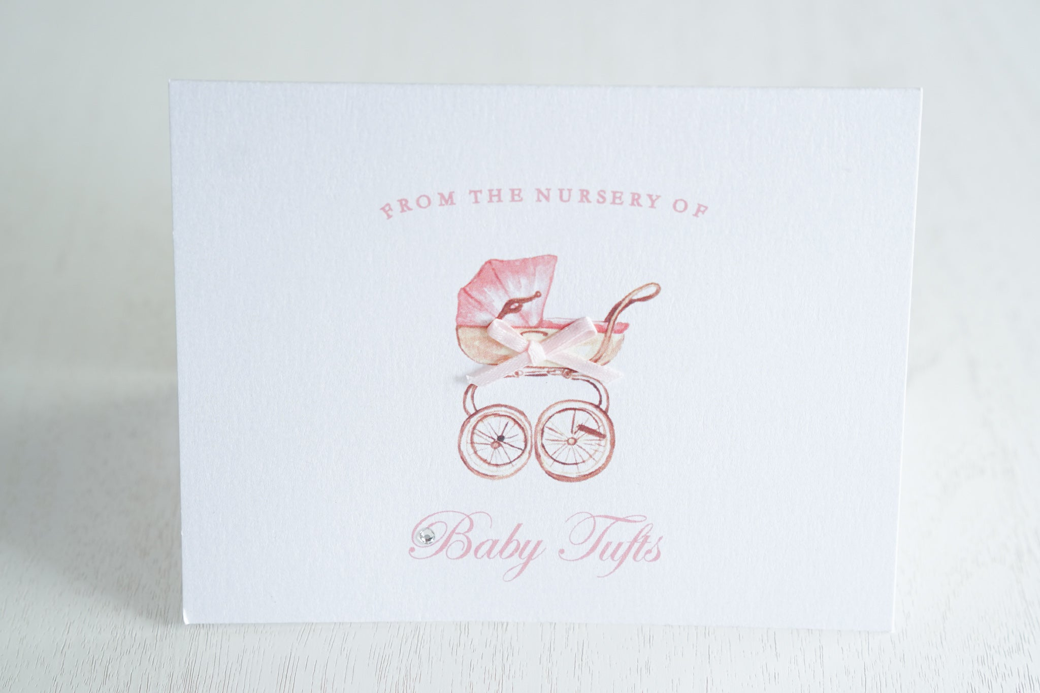 "alt=""Sweet baby thank you card features a white pearlescent shimmer card stock, a pink pram with a rich pink satin ribbon bow and a jewel detail"""