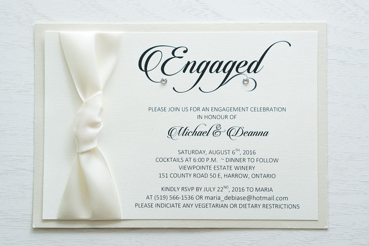 "alt=""Elegant engagement party invitation features an ivory linen stock on an ivory pearlescent shimmer card stock, a rich ivory ribbon knotted bow and Engaged in script with a jewel detail"""
