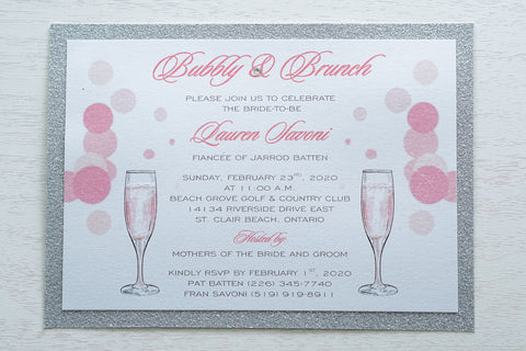 "alt=""Sparkling glitter Bridal Shower invitation features a white pearlescent shimmer card stock on a silver glitter stock, a champagne flutes and bubbly design, jewel detail and glitter sparkle to finish it off"""