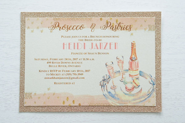 "alt=""Glam glitter Bridal Shower invitation features an ivory pearlescent shimmer card stock on a rose gold glitter stock, an elegant blush pink watercolour border, a prosecco and macaron design and jewel detail to finish it off"""