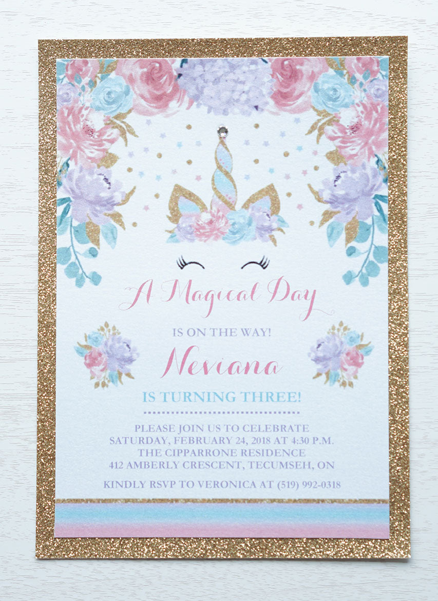 "alt=""Magical birthday party invitation features a white pearlescent shimmer stock on a gold glitter card stock, an elegant watercolour unicorn horn/crown and floral design in pink, purple and teal and is finished with a jewel detail on the tip of the horn"""