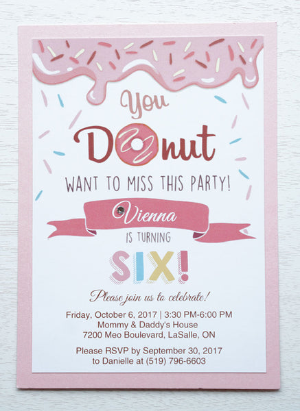 "alt=""Sweet donut birthday party invitation features a matte white stock on a pink pearlescent shimmer card stock, a donut and sprinkle design and is finished with a jewel detail"""