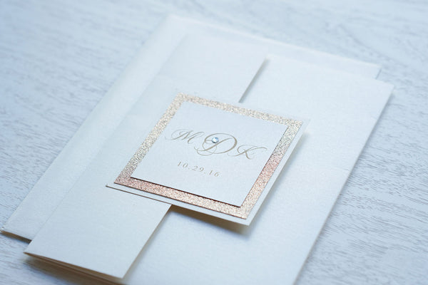"alt=""Elegant ivory pearlescent shimmer pocket fold wedding invitation features an ivory pearlescent shimmer stock on a rose gold glitter stock, gold font and a coordinating tab with monogram/jewel detail to finish it off"""