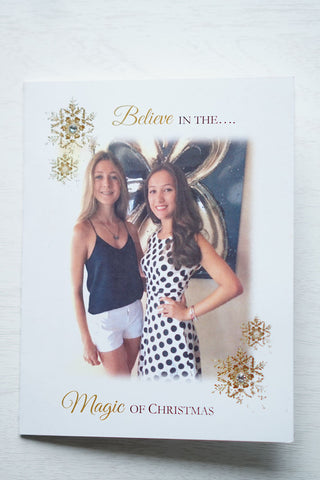 "alt=""This stylish photo card features a white matte card stock, gold snowflakes with jewels, ""Believe in the Magic of Christmas"" printed in gold and black writing and a photo of your choice"""