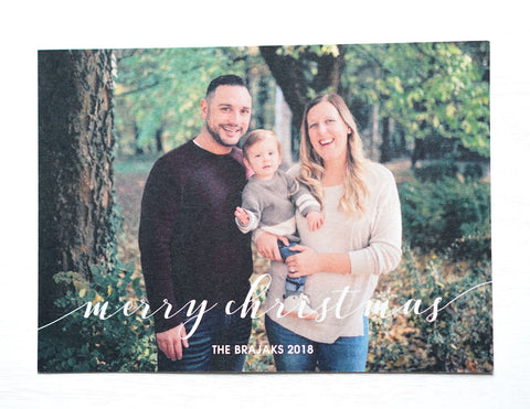 "alt=""This classic photo card features an ivory pearlescent card stock, ""Merry Christmas"" printed with family name and year as well as a photo of your choice on the front. On the back two more photos of your choice can be displayed with a greeting"""