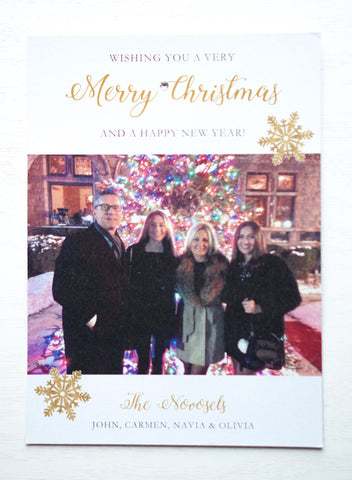"alt=""This modern photo card features a white pearlescent shimmer card stock, gold snowflakes with ""Wishing you a very Merry Christmas and a Happy New Year"" printed in gold and black writing with a jewel detail and includes a photo of your choice"""
