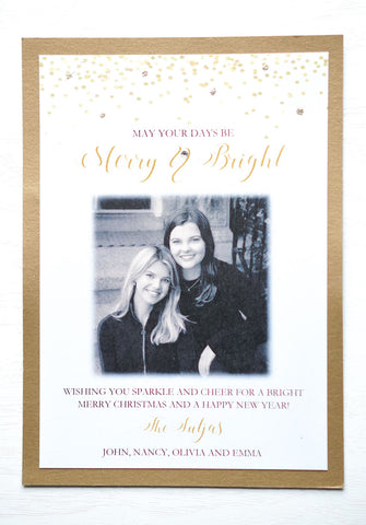 "alt=""This modern photo card features a white matte and antique gold pearlescent shimmer card stock, gold glitter and confetti detail at top with ""May your days be Merry & Bright"" printed below in gold and black writing and a photo and greeting of your choice"""
