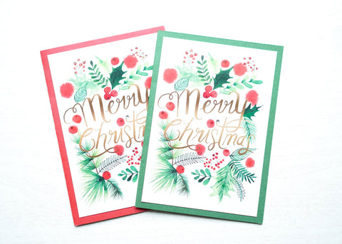 "alt=""This festive Christmas card features a white and red or green pearlescent shimmer card stock, watercolour greenery and is finished with glitter dust and a jewel detail"""