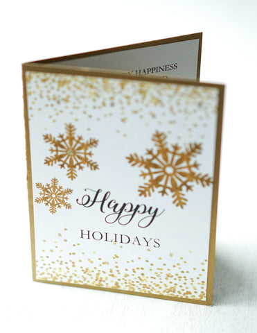 "alt=""This modern card features a white matte card stock on antique gold pearlescent shimmer card stock, gold glitter and confetti, gold snowflakes and ""Happy Holidays"" or ""Merry Christmas"" printed sentiment in black writing"""
