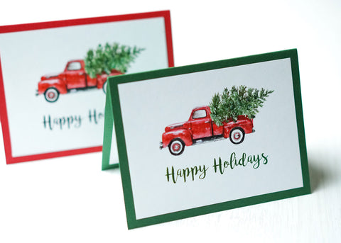 "alt=""This vintage card features a white matte card stock on a green or red pearlescent shimmer card stock, a vintage red truck with tree and glitter dust and ""Happy Holidays"" or ""Merry Christmas"" in a black or green script font"""