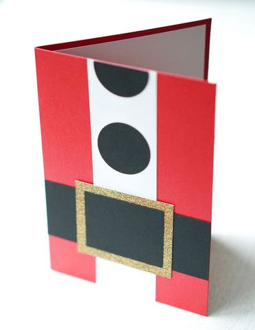 "alt=""This jolly card resembles Santa's suit and features red pearlescent shimmer card stock with black matte card stock for the belt and buttons, gold glitter card stock for the buckle and white matte card stock for the fur"""