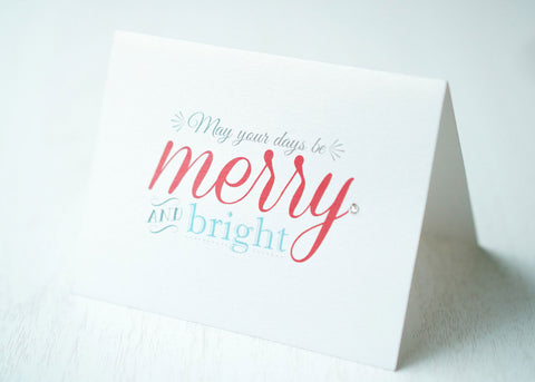 "alt=""This modern card features a white pearlescent shimmer card stock, ""May your days be merry and bright"" printed sentiment in grey, red and blue writing and is finished with a jewel detail"""