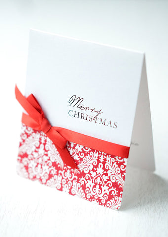 "alt=""This elegant card features a white pearlescent shimmer card stock, ""Happy Holidays"" or ""Merry Christmas"" printed sentiment in pretty script writing with a red damask pattern and is finished with a rich satin red ribbon bow tied around the card"""