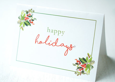 "alt=""This gorgeous Christmas card features a white pearlescent shimmer card stock, ""Happy Holidays"" or ""Merry Christmas"" printed sentiment in pretty script writing with a jewel detail and is framed by a green border, leaves and berries"""