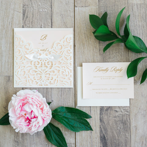 "alt=""Elegant ivory pearlescent shimmer square pocket laser cut wedding invitation features a rich ivory satin ribbon bow and a soft pink pearlescent shimmer card stock insert with monogram and jewel detail and gold font"""