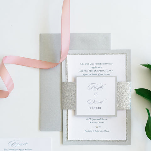 "alt=""Modern wedding invitation features a white pearlescent shimmer card stock layered onto silver glitter and pearlescent shimmer stock layers, a jewel detail and a coordinating belly band with couple's names and wedding date"""