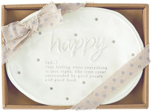 "alt=""Oval ceramic plate has a hand-painted polka dot pattern with the word ""happy"" in raised lettering. The debossed definition says ""(adj.) that feeling when everything is just right; like time spent surrounded by good people and good food"". Comes in a brown gift box with ribbon tied around"""