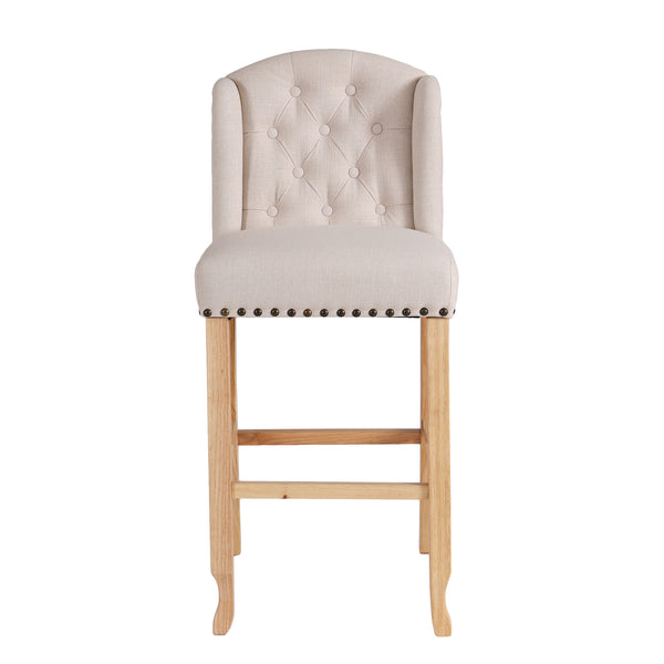 Front view image of a beige fabric bar stool with studded detail and oak legs