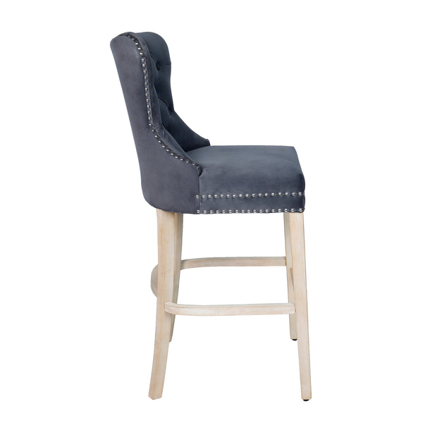 Side view image of a grey fabric bar stool with studded detail and oak legs