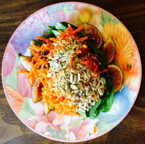 carrot and raisin salad with sunflower seeds, hemp seeds, and figs over greens.