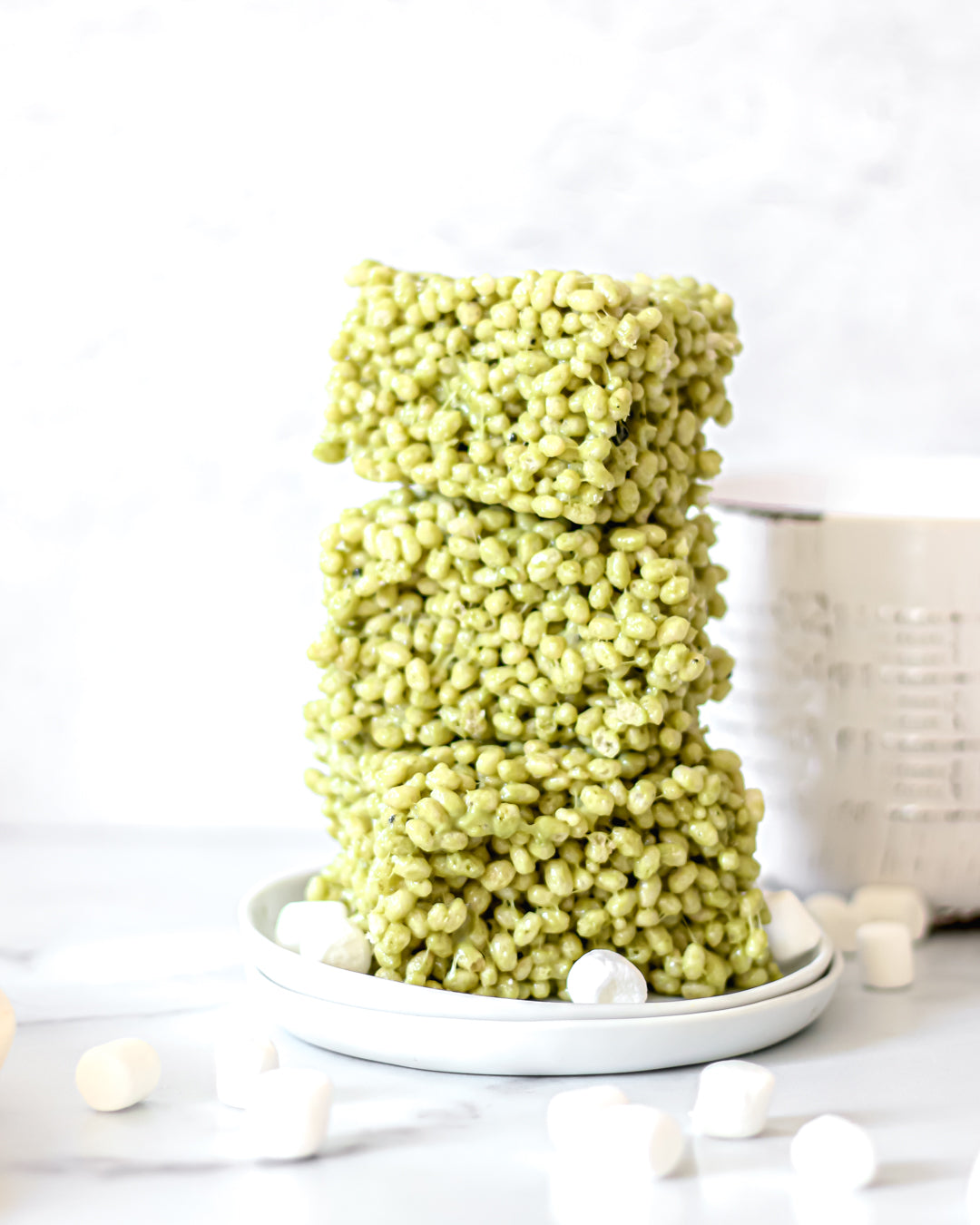 Photo of a stack of 3 rice krispies treats squares made with green tea powder, set on a white plate, with a few small marshmallows strewn about, all on a white background