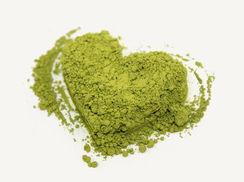 Photo of heart-shaped matcha green tea powder on white background