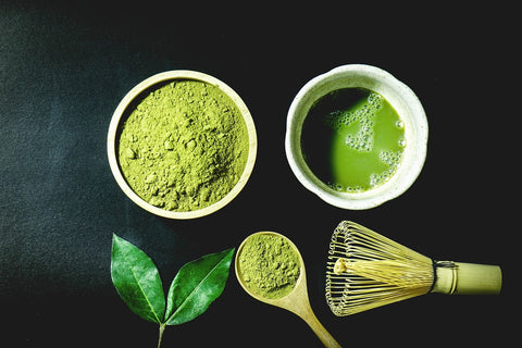 Photo of a traditional ceremonial matcha tea set, including matcha green tea powder in a small bowl, prepared matcha liquid tea in a small white cup, a wooden spoon holding a small amount of matcha powder, and a Japanese bamboo whisk, all on a dark background.