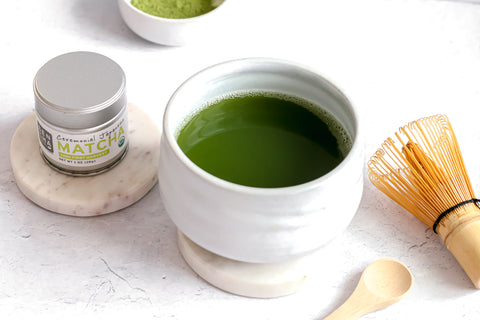 Photo of a small silver tin of Sencha Naturals Ceremonial Grade Matcha Powder on the left, a small white cup of liquid green tea in the center, and a small wooden spoon and bamboo whisk on the right, all on a white background