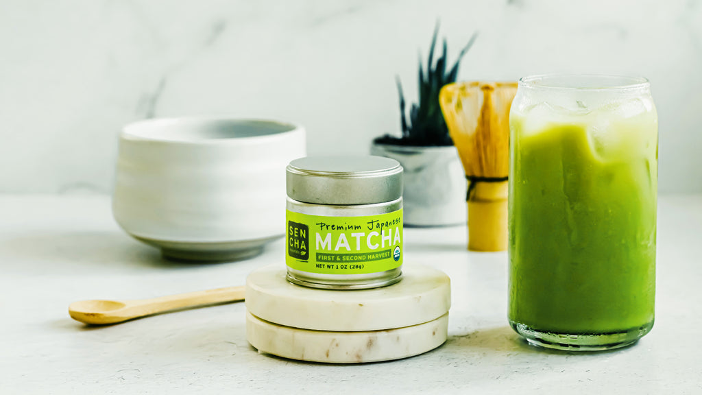 Photo of Sencha Naturals Premium Matcha tin, a small white cup, and an Iced Latte in a clear glass, all on a white background with a bamboo whisk and a green plant in the back