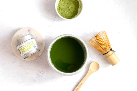 A photo of an arrangement of green tea items, including a small silver tin of Sencha Naturals matcha green tea powder on the left, a small bowl of matcha green tea powder on the top center, a small cup of liquid green tea on the bottom center, a small wooden spoon on the right, and a bamboo whisk above the spoon.