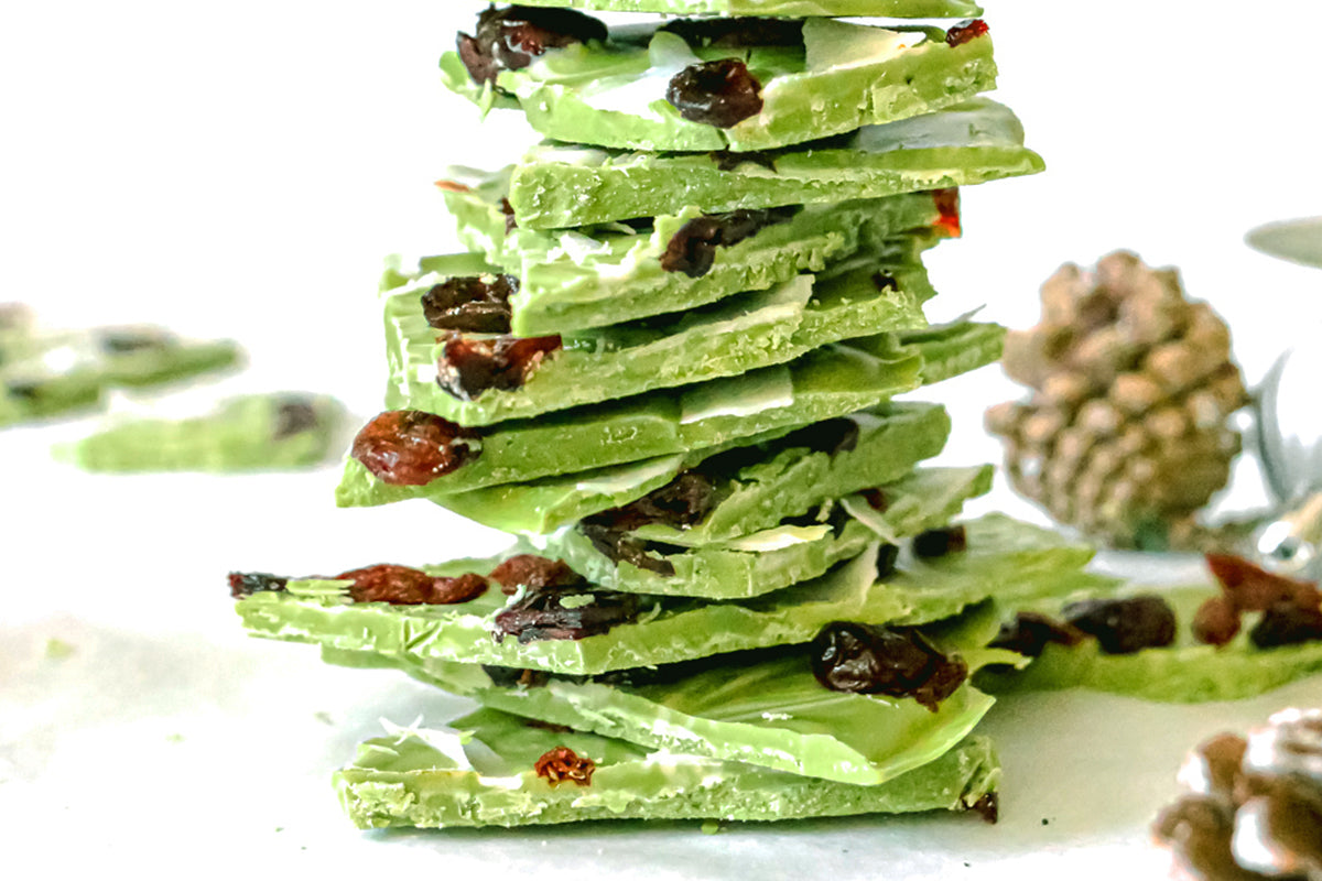 Photo of a stack of pieces of green tea Holiday Bark dessert treats topped with cranberries and white coconut strips, all on a white background