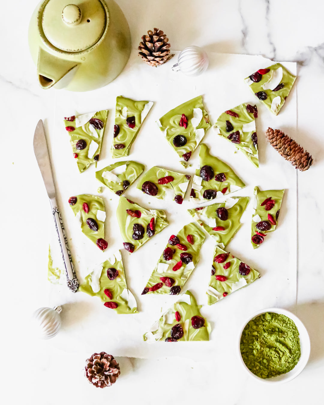 Photo of several pieces of green tea Holiday Bark dessert treats, topped with cranberries and white coconut strips, surrounded by a few decorative pine cones, a small green teapot, a small bowl containing matcha green tea powder, a silver butter knife, and two white Christmas globes, all on a white background