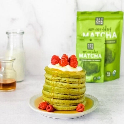 Photo of a stack of green tea pancakes covered with raspberries and maple syrup on a white plate, with a bag of Sencha naturals matcha green tea powder in the back, a clear jar of milk in the back left, a small clear bottle of maple syrup next to the milk, all on a white background