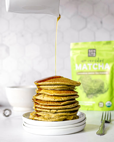 Photo of a stack of pancakes made with matcha green tea powder, with maple syrup being poured on top, and a bag of matcha green tea in the background, all set on a white countertop.