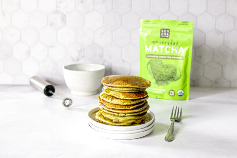 Photo of a stack of pancakes made with matcha green tea powder, with a silver fork on the right, a small silver electric whisk and white bowl in the back, and a bag of matcha green tea in the background, all set on a white countertop.