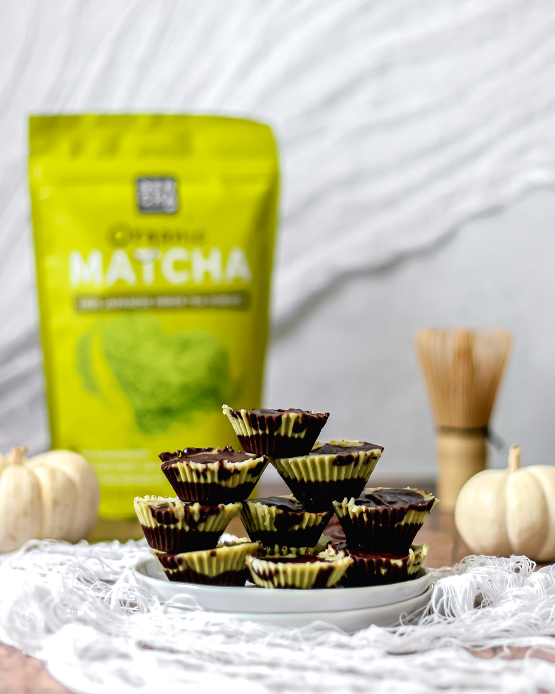 Photo of Sencha naturals matcha green tea powder in a bag, a stack of chocolate matcha dessert cups in the foreground, as well as a bamboo whisk in the back along with some small white decorative pumpkins, all on a white background