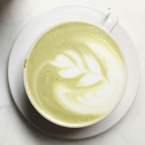 Photo of green tea latte in a white mug on a white background