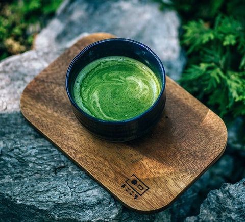 Photo of matcha green tea in a dark cup on a wooden board