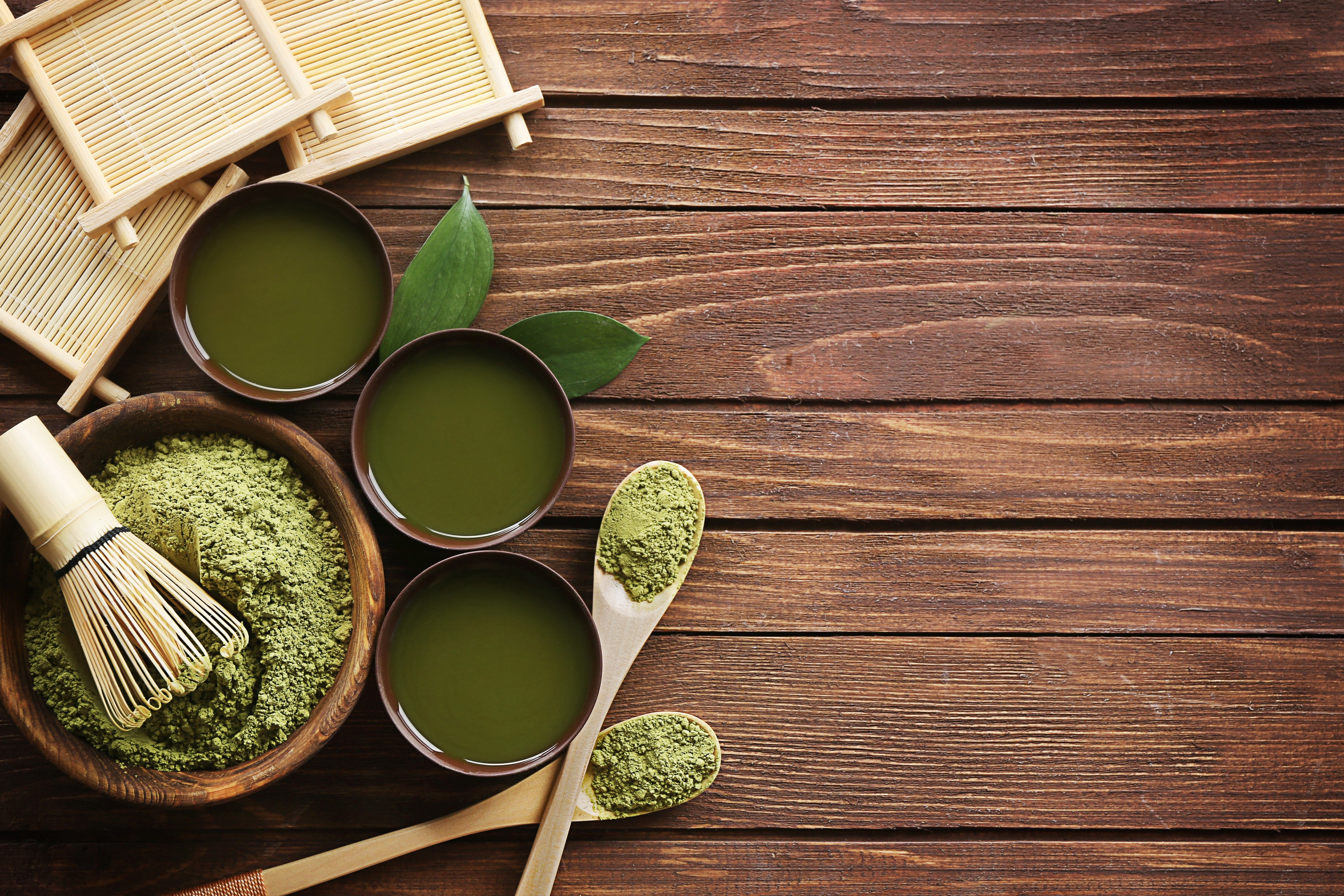 Photo of a small bowl containing green tea powder with a bamboo whisk on top, 2 small wooden spoons to the right, 3 light wooden coasters, and 3 cups of liquid green tea all on a dark wooden tabletop